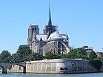 The Seine River flows around an island with a gray stone gothic cathedral rising above the island.