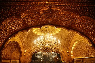Golden Temple - Interior of Darbar Sahib with gold encrusted walls featuring a golden chandelier.