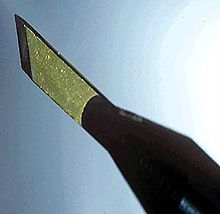 A diamond scalpel consisting of a yellow diamond blade attached to a pen-shaped holder