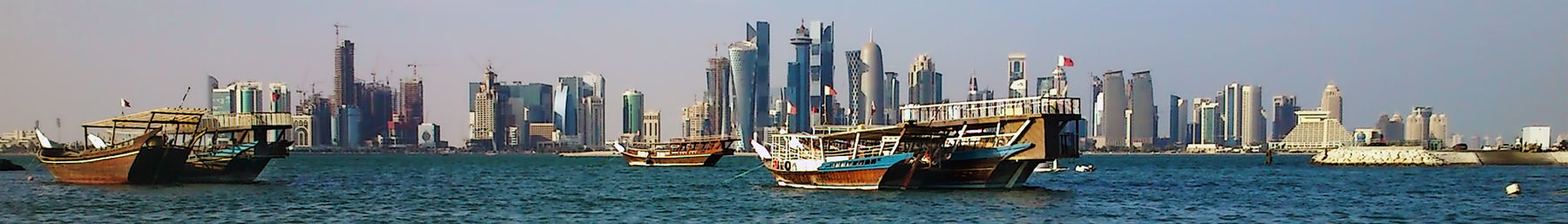 A view of traditional dhow boats in front of the glimmering Doha Corniche
