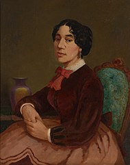Oil painting portrait of Christiana Bannister. She sits on an upholstered chair and wears a brown skirt and blouse, with a red bow at her throat. She is clasping her hands and resting them on a nearby table.