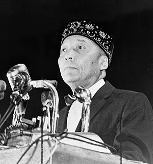 Elijah Muhammad standing behind microphones at...
