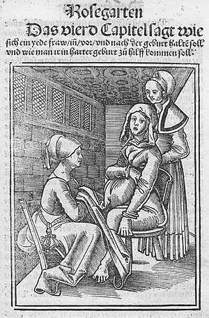 Obstetrics - Two midwives assisting a woman in labour on a birth chair in the 16th century, from a work by Eucharius Rößlin.