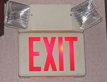 An exit sign in the United States, showing the way to the nearest exit, with two emergency lights for electrical failure.