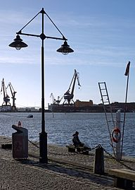 Fisherman having a smoke on the docks by Göta älv.jpg