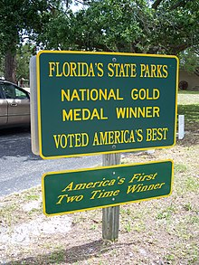 two green signs with yellow border and lettering about Florida State Parks