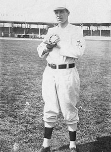 "A man in a white baseball uniform with an overlapping ""STL"" on the left sleeve stands with his fists together wearing a glove on his left."