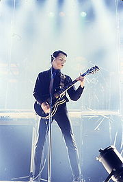 A colour photograph of Gary Numan performing onstage with a guitar and microphone