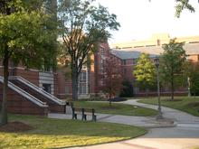 Un ladrillo rojo y cemento blanco, edificio de apartamentos de cuatro pisos con un patio ajardinado en el primer plano