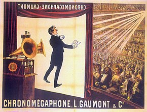 "Illustration of a theater from the rear Right of the stage. At the front of the stage a screen hangs do orming. In the foreground is a gramophone with two horns. In the background, a large audience is seated at orchestra level and on several balconies. The words ""Chronomégaphone"" and ""Gaumont"" appear at both the bottom of the illustration and, in reverse, at the top of the projection screen."