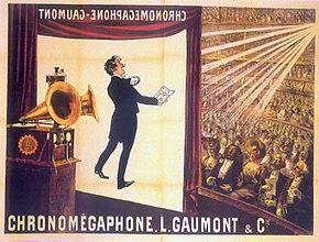 """Sahnenin sağ arka tarafından bir tiyatro resmi.  Sahnenin önünde bir ekran orming yapıyor.  Ön planda iki boynuzlu bir gramofon var.  Arka planda, orkestra seviyesinde ve birkaç balkonda geniş bir seyirci oturuyor.  """"Chronomégaphone"""" ve """"Gaumont"""" kelimeleri hem çizimin altında hem de ters olarak projeksiyon ekranının üstünde görünür."""