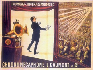 "Illustration of a theater from the rear Right  of the stage. At the front of the stage a screen hangs down with the projected image of a tuxedoed man holding up a text and performing; in the foreground is a gramophone with two horns. In the background, a large audience is seated at orchestra level and on several balconies, the words ""Chronomégaphone"" and ""Gaumont"" appear at both the bottom of the illustration and, in reverse, at the top of the projection screen."