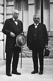 Twee mannen met snorren en elk gekleed in donkere pakken staan glimlachend op de trappen van een gebouw: links is de man kaal, met een lichte hoed en een wandelstok in zijn linkerhand;  aan de rechterkant is het individu kleiner, heeft grijs-wit haar en houdt een donkere hoed in zijn linkerhand