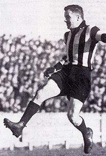 A dark-haired footballer in a kicking motion wearing a long-sleeve black-and-white vertically-striped guernsey, dark shorts and football boots