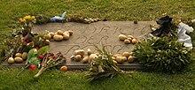 Grabstein Friedrichs des Großen mit darauf gelegten Kartoffeln zum Andenken an den Kartoffelbefehl (Quelle: Wikimedia)