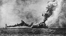 A large warship is almost completely obscured by a huge column of smoke.