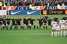 Rugby team wearing all black, facing the camera, knees bent, and facing toward a team wearing white