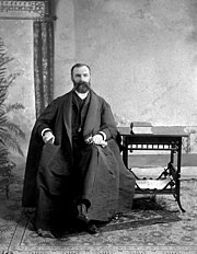 A posed formal shot of Wilson, who is seen as a young man, though with full beard and mustache. He sits next to a table on which is a book, and wears a long coat or cape which extends well around him.