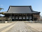 Large wooden building with tile roof.