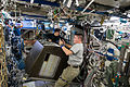 ISS-45 Kimiya Yui and Kjell Lindgren work on a storage rack inside the Destiny lab.jpg