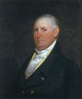 A gray-haired man with a sullen expression wearing a high-collared white shirt, gold vest, and black jacket with gold buttons