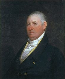 A stern-looking man with thinning, white hair wearing a white shirt and black coat with gold buttons