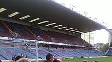 "A two-tiered cantilever football stand. The lower tier has light blue seats with some claret seats which spell the word ""Clarets"". The upper has all claret seating with light blue seats spelling ""Burnley""."