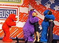 Jill Biden and Michelle Obama greet Sesame Street Muppets Telly and Grover while Elmo waits for his hug, 2011.jpg