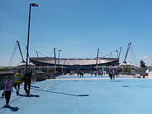 A straight tarmac road. At the head of the road is a stadium with a bowl-shaped outline, surrounded by a number of masts, with cables running to the stadium roof.