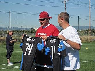 Alex Smith - Smith and Joe Staley holding MLS jerseys