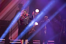 Kelly Clarkson performing with a accompanying band in a strobe-lit stage