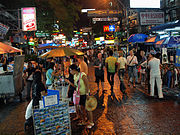 """Night scene on a pedestrian street, with many people and street vendors; shops along the street bearing brightly lit signs with names like """"99Fashion"""", """"Brick Bar"""", """"Mulligans Irish Bar"""", and Pepsi and McDonald's logos"""