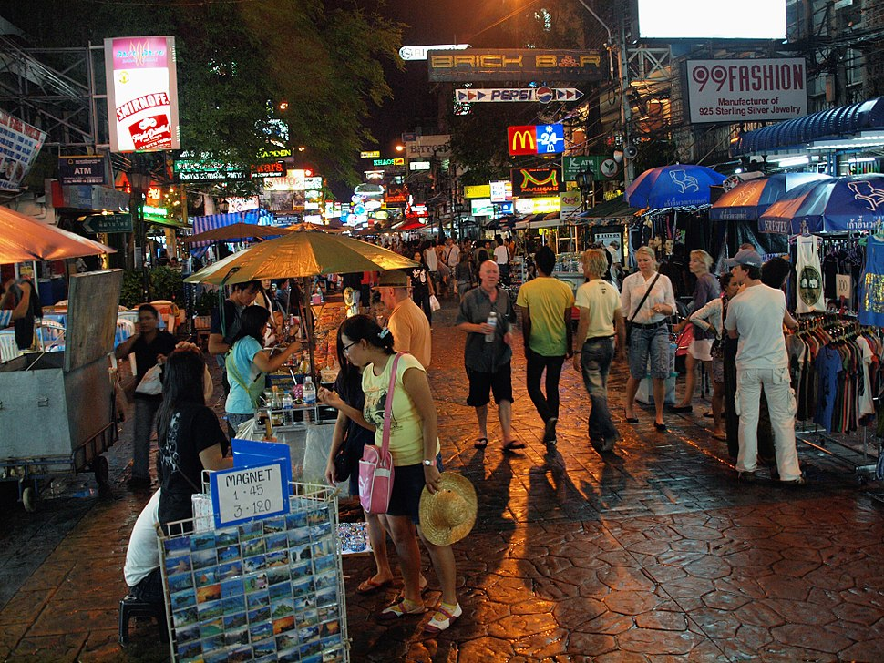 "Night scene on a pedestrian street, with many people and street vendors; shops along the street bearing brightly lit signs with names like ""99Fashion"", ""Brick Bar"", ""Mulligans Irish Bar"", and Pepsi and McDonald's logos"