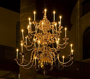English: A antique chandelier lit up by candle...