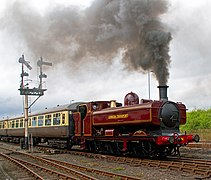 "A pannier tank locomotive is pulling two cream and brown passenger carriages. The locomotive is mainly painted maroon, but there is black and yellow lining on the side of the pannier tank, the cab, the bunker, the toolbox, and the splashers. The words ""LONDON TRANSPORT"" are shown in yellow on the side of the pannier tank. The chimney and front of the smokebox are black. The front buffer beam is red."
