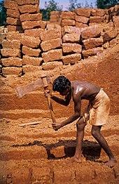 Een man snijdt lateriet in baksteenstenen in Angadipuram, India.