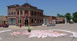 One- and two-story brick buildings seen across a street intersection; crowned eagle painted on the pavement, filling most of the intersection