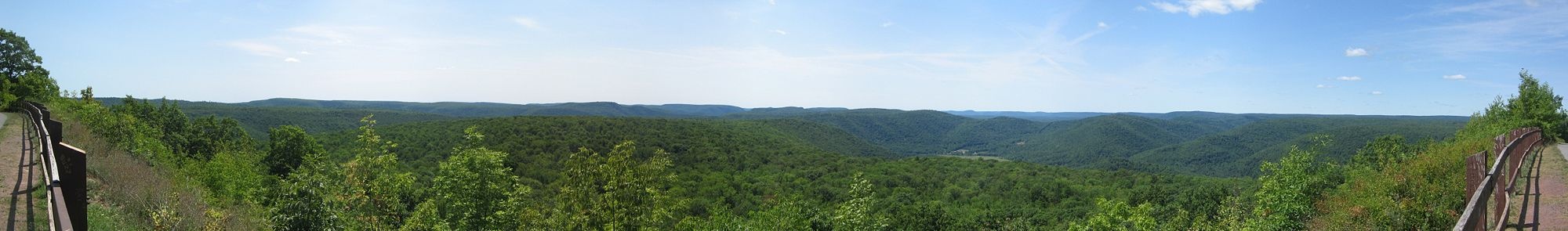 View from a fenced overlook of wooded low mountains whose peaks are all nearly the same height