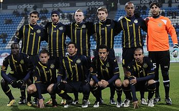 A modern association football team lines up for a pre-match photograph. Five players squat in front of a line of six, which stands. All of the players wear a dark blue uniform with yellow markings, apart from the player to the extreme right of the standing row, who wears an orange shirt with black shorts and socks. He also wears a pair of white gloves, indicating that he is the team's goalkeeper.