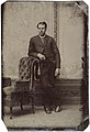 Man standing by chair, ca. 1856-1900. (4731904491).jpg