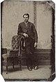 Man standing by chair, ca. 1856-1900. (4731904491).jpg