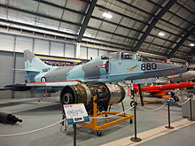 Colour photograph of a military fighter jet aircraft painted in blue and grey camouflage in a museum, with other aircraft and engines visible