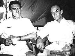 An informal photograph featuring two men sitting beside each other on wooden chairs. Both are wearing white naval uniforms and appear to be in a tent. The man on the left has dark, slightly curly hair, his arms are semi-crossed with a mug in his right hand and a watch on his left wrist. He is not looking at the camera. The other man has short hair and is slightly balding. He has his arms resting on the chair's arm rests and is looking at the camera.
