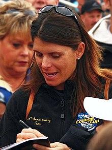 portrait en buste d'un femme signant un autographe.