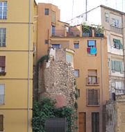 Torre de la murada àrab del segle XI, envoltada d'edificis (actual barri del Carme, a Ciutat Vella). És una de les poques restes del període musulmà de València