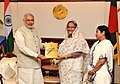 Narendra Modi presents to the Prime Minister of Bangladesh, Ms. Sheikh Hasina, a transcript of Parliamentary debates on LBA, in Dhaka, Bangladesh. The Chief Minister of West Bengal, Kumari Mamata Banerjee is also seen.jpg