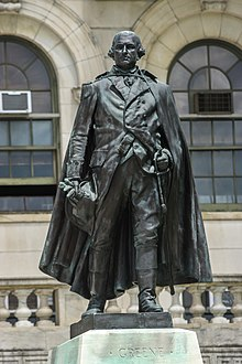 A nearly black bronze statue General Nathanael Greene in uniform, stepping forward with a hand on his sword