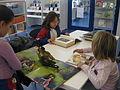 Nens llegint i mirant llibres a la Bibiloteca.JPG