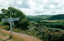 White signpost on a path on the left. To the right are rolling green fields on the hillsides.