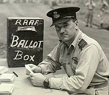 "Man in military uniform with peaked cap seated at a desk beside a box marked ""RAAF Ballot Box"""